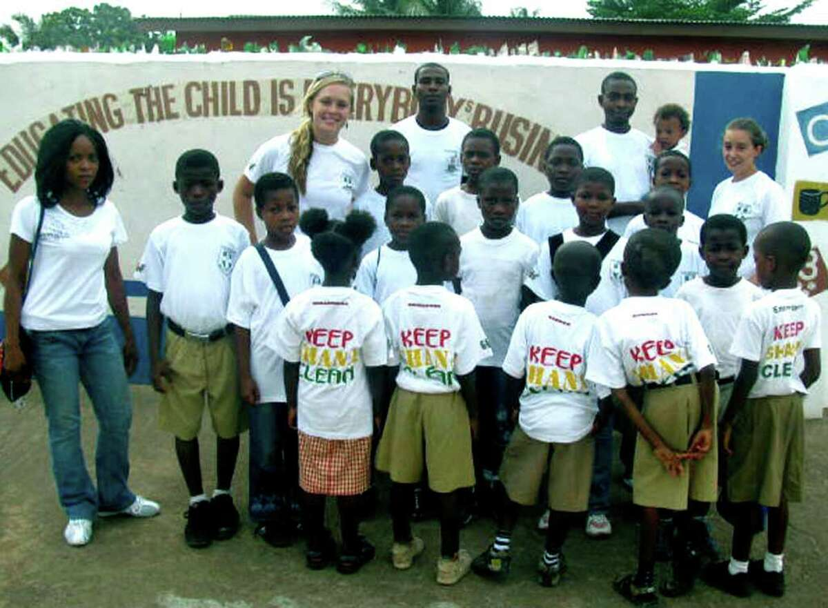 """SPECTRUM/Kristin Collins, back left, and Jaymie Lanera, back right, pose for a photo with volunteers and students from Kiddy Kare headed out for a day dedicated to their ìKeep Ghana Cleanî project, held in partnership with the BrainBirds Academy in Ghana. """"We walked around and picked up trash and recycling, taught students about the importance of living in a clean, healthy environment,"""" said Ms. Collins. For their efforts, the group was featured on the local news that day. Courtesy of Kristin Collins"""