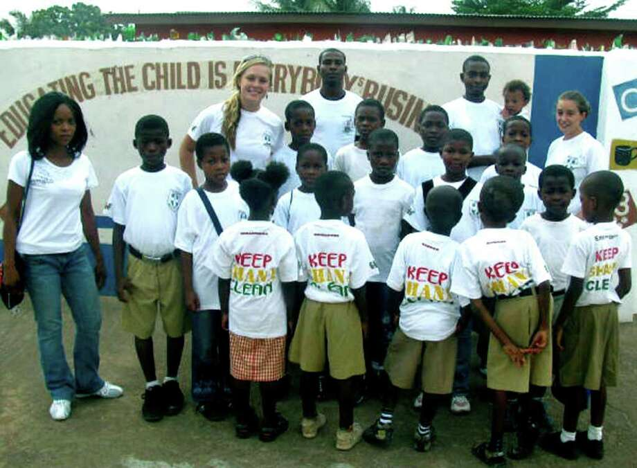 "SPECTRUM/Kristin Collins, back left, and Jaymie Lanera, back right, pose for a photo with volunteers and students from Kiddy Kare headed out for a day dedicated to their ìKeep Ghana Cleanî project, held in partnership with the BrainBirds Academy in Ghana. ""We walked around and picked up trash and recycling, taught students about the importance of living in a clean, healthy environment,"" said Ms. Collins. For their efforts, the group was featured on the local news that day.  Courtesy of Kristin Collins Photo: Contributed Photo"