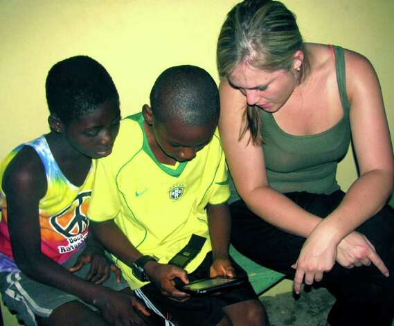 SPECTRUM/Augustina, left, and Jeffrey, students in Abokobi, Ghana, are shown how to use an e-Reader by Kristin Collins of New Milford. 2011.  Courtesy of Kristin Collins Photo: Contributed Photo