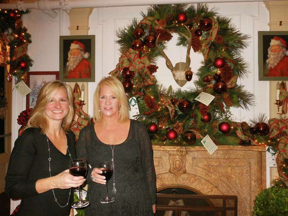 Stephanie Markowich and Kelly Sohigian, both of Fairfield, decorated the Gentleman's Library Room at the Burr Homestead, one of the many rooms decorated for the 30th annual Fairfield Christmas Tree Festival. Photo: Mike Lauterborn / Fairfield Citizen contributed