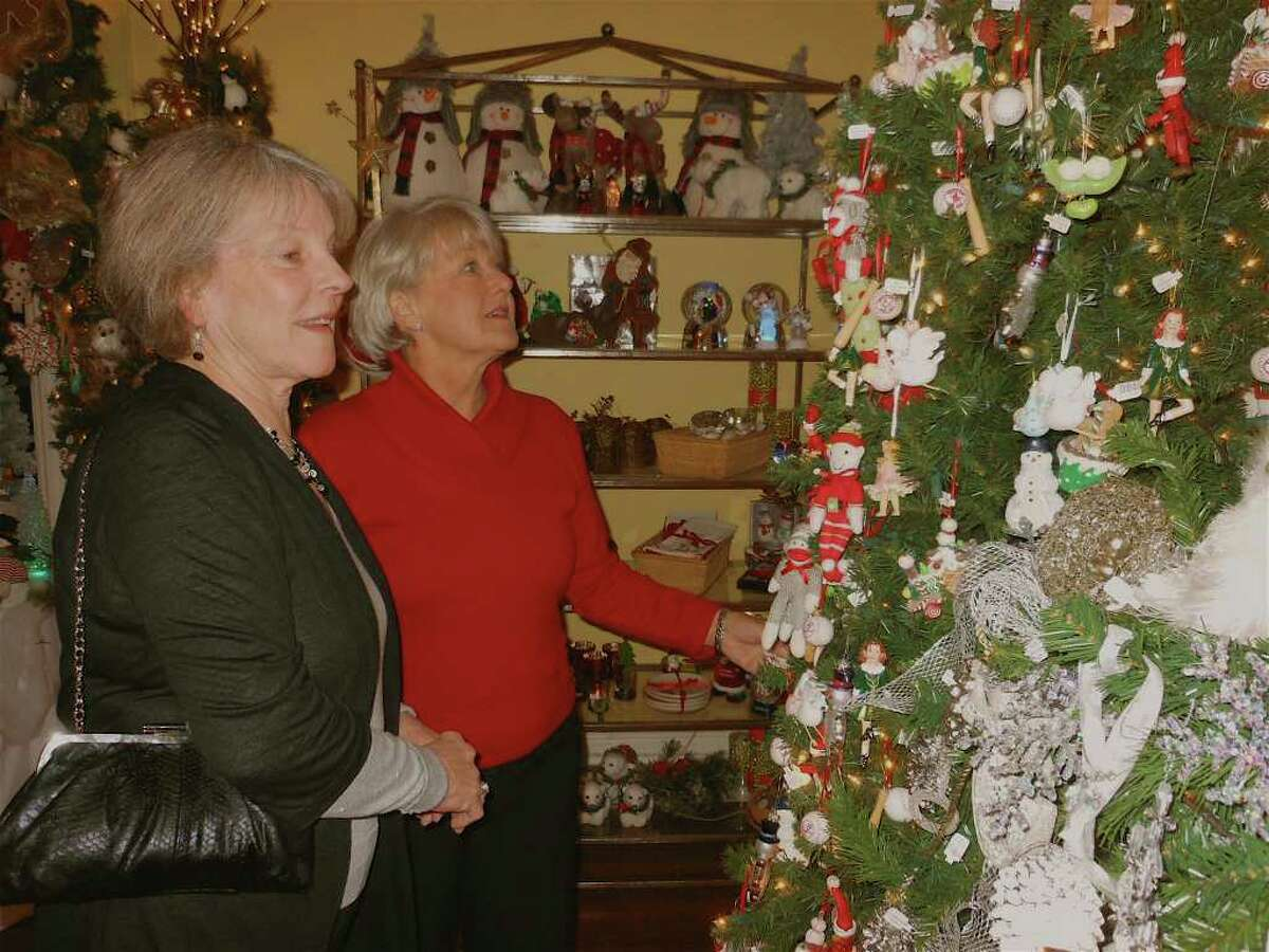 Fairfielders Susan Burns and Linda Lanzo look at ornaments hanging on a Christmas tree in the Holiday Boutique room at the Fairfield Christmas Tree Festival on Thursday night.