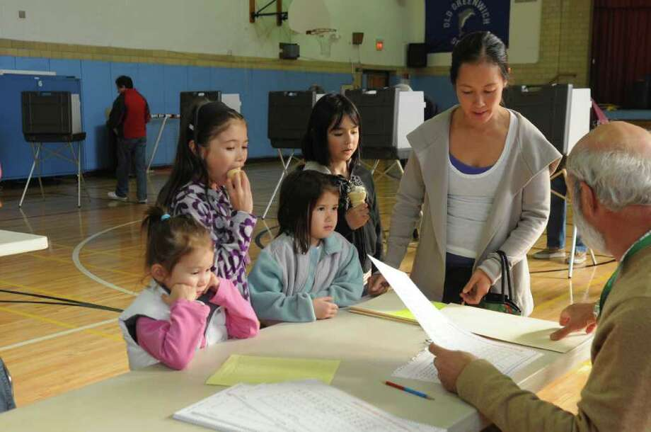 Tracia Luh votes at the Old Greenwich School polling station Nov. 8, 2011, while her daughters and a family friend look on. Photo: Helen Neafsey, Greenwich Time File / Greenwich Time