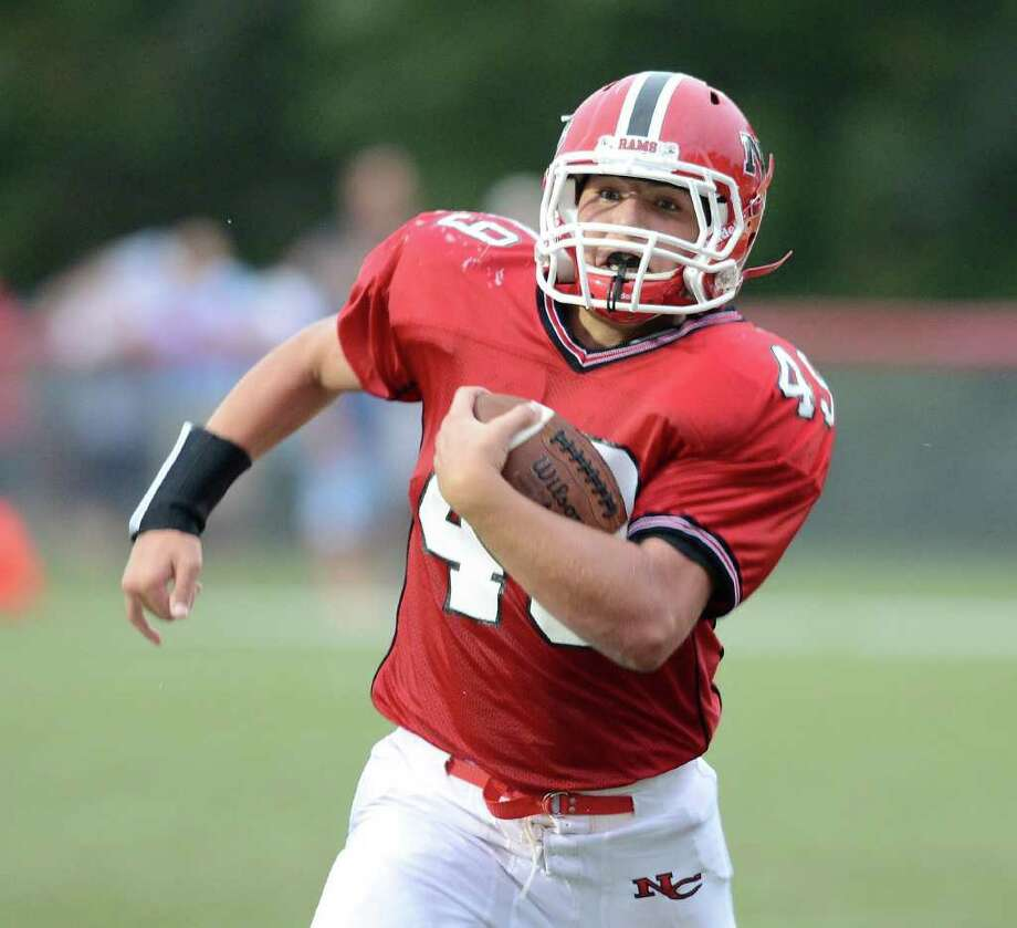 New Canaan's #49 Kevin Mcdonough runs in a first half touchdown as New Canaan High School hosts Trinity Catholic High School in varsity football in New Canaan, CT on Saturday September 24, 2011. Photo: Shelley Cryan / Shelley Cryan freelance; Stamford Advocate freelance