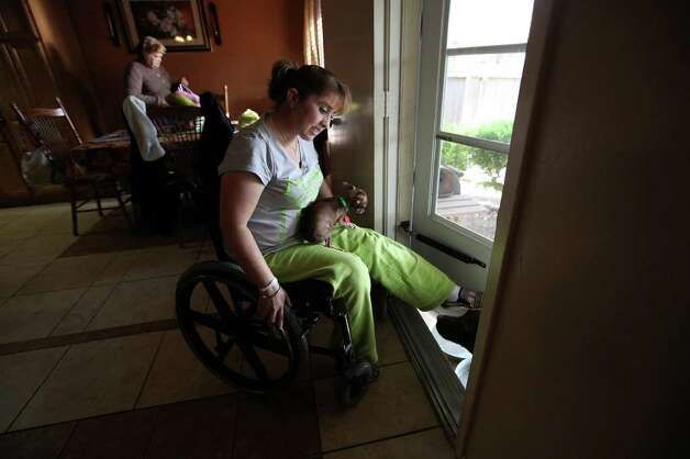 Patricia Sanchez-Lopez plays with her dogs Bibi and Mocha in her San Antonio home. Sanchez-Lopez suffered a spinal cord injury in a 2009 crash. With help from Project MEND, she was able to get a wheelchair, hospital bed and scooter. Photo: JERRY LARA, San Antonio Express-News / SAN ANTONIO EXPRESS-NEWS