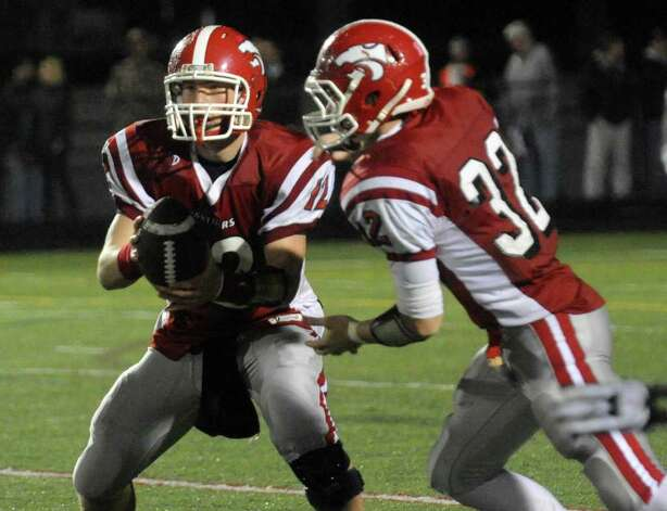 Masuk QB Casey Cochran hands the ball off to #32 Colin Markus. Photo: Christian Abraham / Connecticut Post