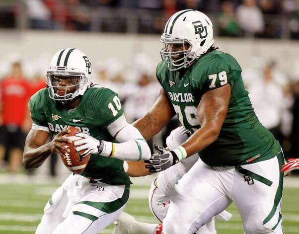 "Baylor quarterback Robert Griffin III (left), running past right guard Robert ""Big Griff"" Griffin, could lock up the Heisman Trophy depending on how he plays today against UT. Photo: SHARON ELLMAN, ASSOCIATED PRESS"