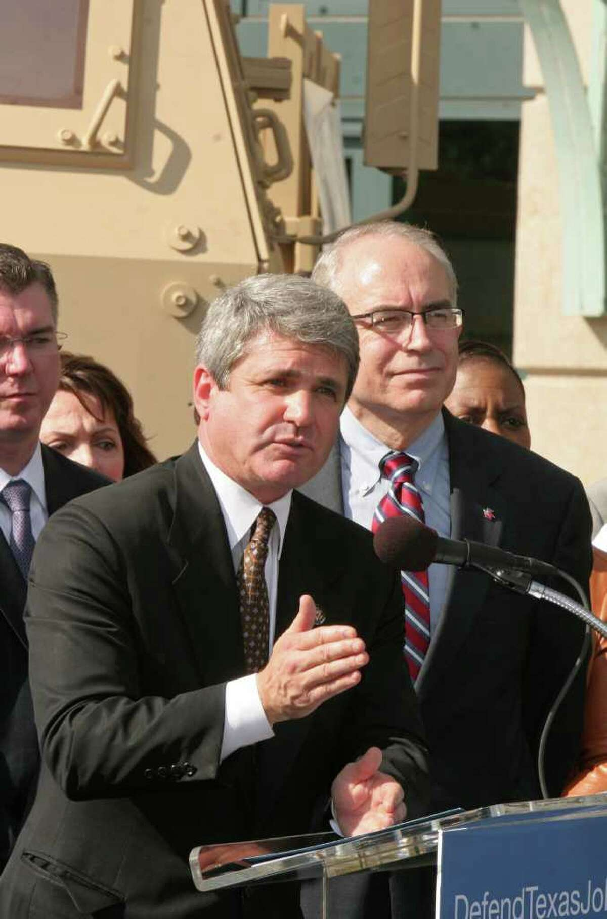 (For the Chronicle/Gary Fountain, November 23, 2009) Congressman Michael McCaul, left, talking about the bidding process that has taken away a contract to build military armored vehicles at a Sealy plant and the cost to the region's economy. At right, is Jeff Moseley, president and CEO of Greater Houston Partnership. In the background are 17 of the Army's Family of Medium Tactical Vehicles (FMTV), representing one for each year they have been building them. The press conference was at Minute Maid Park.