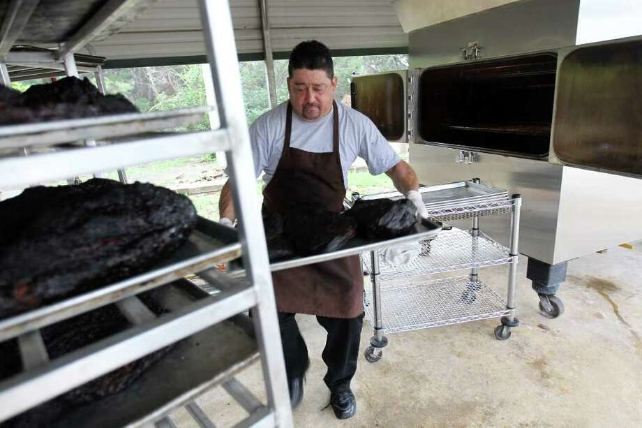Tom Hernandez pulls 500 pounds of brisket from the smoker for upcoming Christmas parties at Pedrotti's Ranch. Photo: JENNIFER WHITNEY, Jennifer Whitney/ Special To The Express-News / Jennifer Whitney/special to the Express-News