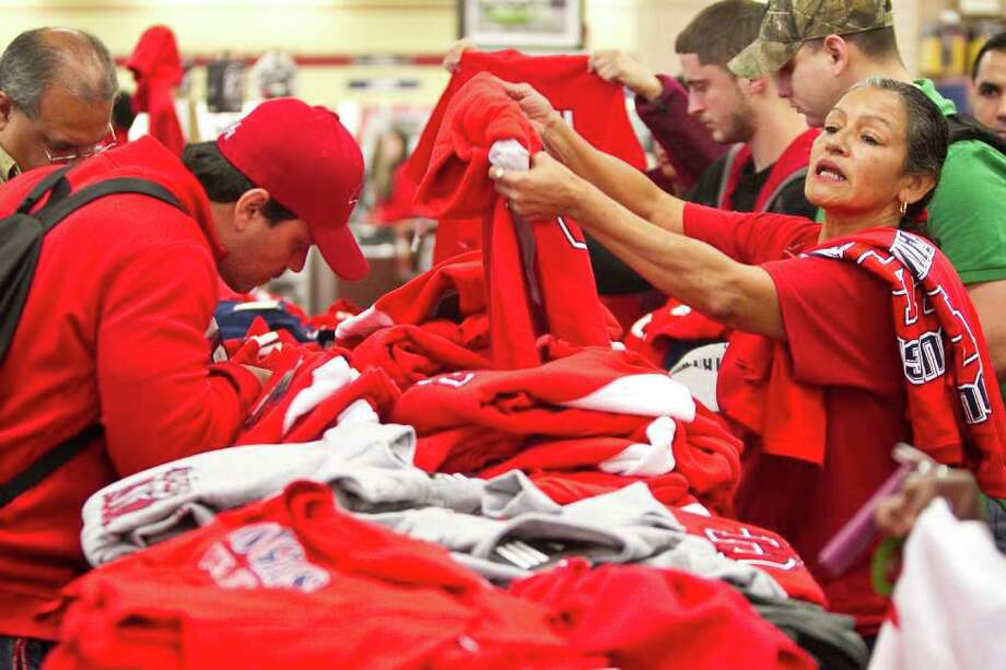 Mary Martinez, a staff member of the University of Houston's college of optometry, sifts through a pile of shirts during the University of Houston Bookstore's 'Get Your Red On' sale. Photo: Nick De La Torre, Houston Chronicle / © 2011  Houston Chronicle