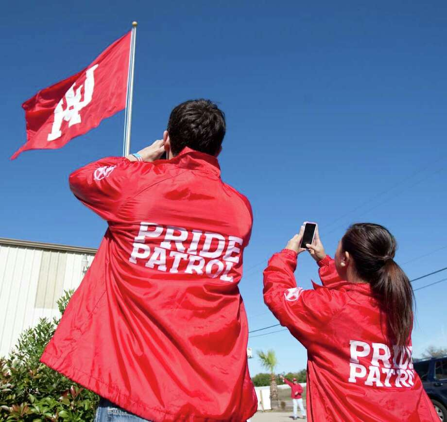 University of Houston Pride Patrol spirit club members Sason Tavakoli, left, a senior from Houston, and Kate Gavila, a junior from Houston, photograph a brand new UH flag. Photo: Nick De La Torre, Houston Chronicle / © 2011  Houston Chronicle