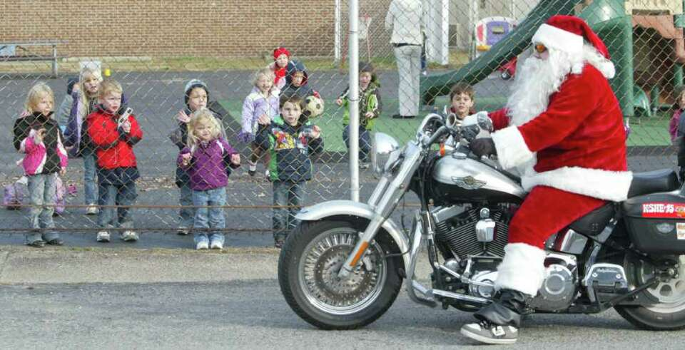 Uriah Cole rides a Harley Davidson motorcycle dressed as Santa Claus past children at Toddler Town i