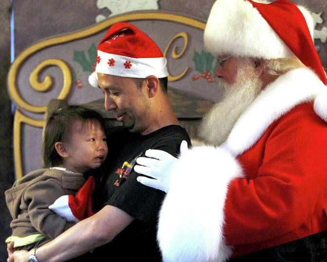 Iris Yeh, 2 1/2, cries as she gets her first photo taken with Santa, as her dad, Michael Yeh, holds