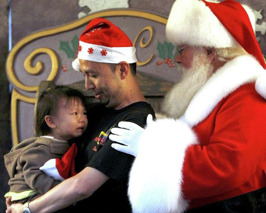 Iris Yeh, 2 1/2, cries as she gets her first photo taken with Santa, as her dad, Michael Yeh, holds her at the Santa photo booth set up at the annual Mayor's Holiday Celebration presented by Reliant, an NRG company, at City Hall. Photo: Karen Warren, Houston Chronicle