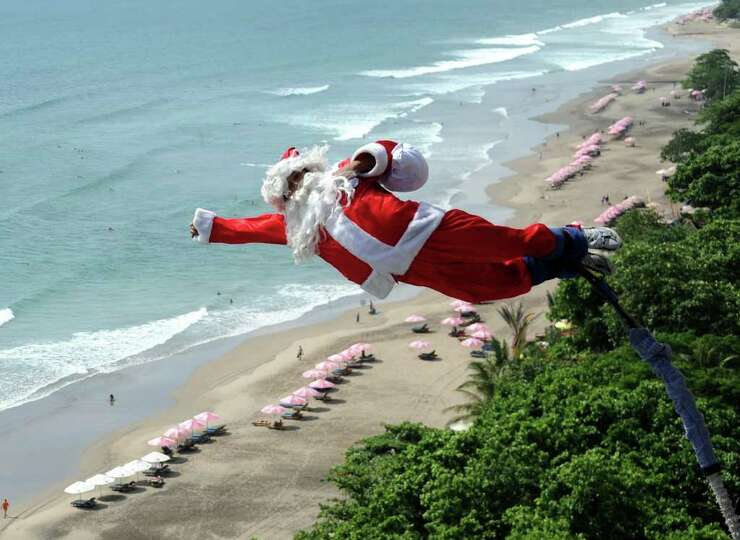 A bungee jumper dressed as Santa Claus leaps from a platform above Kuta  beach, Denpasar on Indonesi