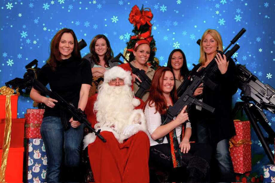 This undated photo provided by the Scottsdale Gun Club shows people posing with Santa Claus and several automatic weapons at the Scottsdale, Ariz. club. Photo: Gordon Murray, Associated Press / Scottsdale Gun Club
