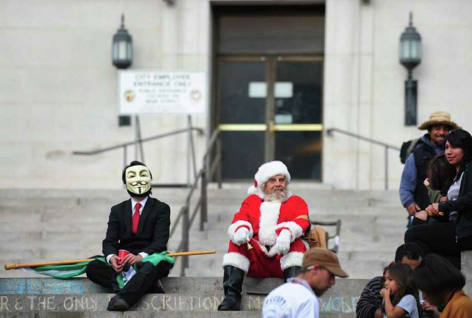 Two men, one dressed as Santa Claus and the other wearing a suit and a Guy Fawkes mask, sit on the steps to City Hall in downtown Los Angeles  overlooking where anti-Wall Street demonstrators have been camped out since early October on November 28, 2011. Photo: FREDERIC J. BROWN, Getty / AFP