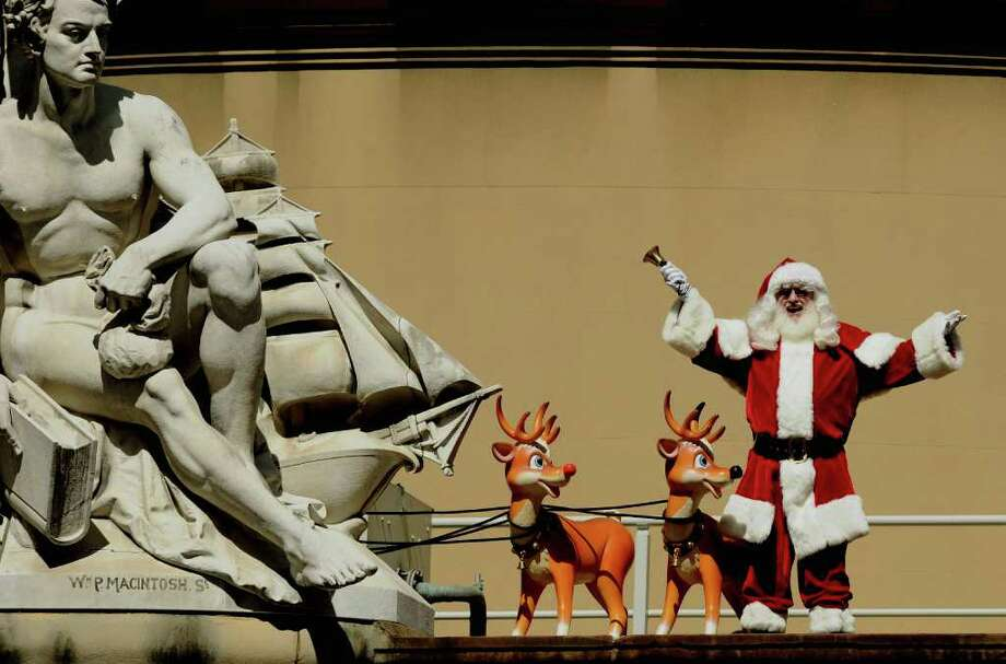 Santa Claus waves from the roof of Sydney's iconic Queen Victoria Building (QVB) on November 28, 2011.  This Christmas for the first time ever Santa Claus will be in residence inside the massive Romanesque QVB, which contains a range of boutique shops and underwent a major refurbishment in 2009. Photo: GREG WOOD, Getty / AFP