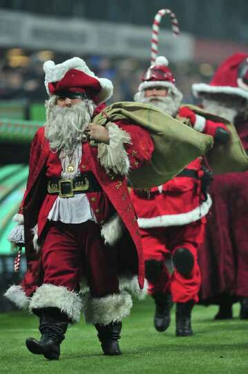 People dressed as Santa Claus walk on the pitch prior the Italian Serie A football match between AC