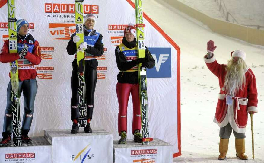 Santa Claus (R) greets (FromL) Austrian winners, second-placed Gregor Schlierenzauer, winner Andreas