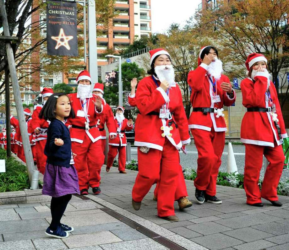 "Santa Claus trainees of the ""Santa Claus academy"" take part in a parade in Tokyo on November 27, 2011. Photo: YOSHIKAZU TSUNO, Getty / AFP"