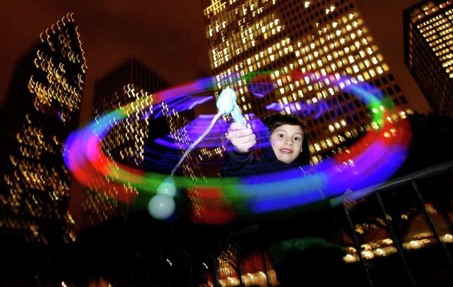 Michael Gonzalez, 6, plays with his lighted toy during the annual Mayor's Holiday Celebration and Tree Lighting presented by Reliant at City Hall, Dec. 2, 2011. Officials said that over 15,000 people attended the event, which is a holiday tradition of music, fireworks, Santa and the Lighting of the Official Holiday Tree. Photo: Karen Warren, Houston Chronicle / © 2011 Houston Chronicle
