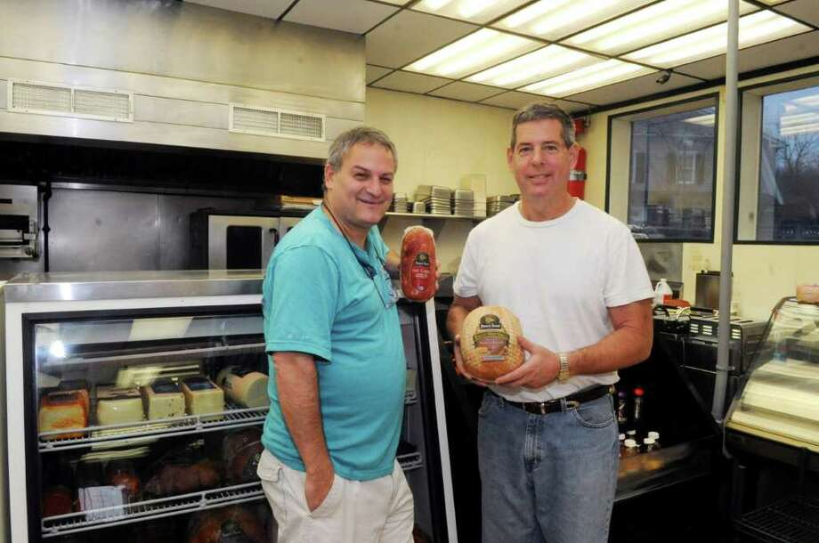 Brian Abel and Steve Montello, co-owners of the forthcoming Abello's deli in Darien, getting their delicatessen ready for opening Tuesday, Nov. 29, 2011. Photo: Helen Neafsey / Greenwich Time