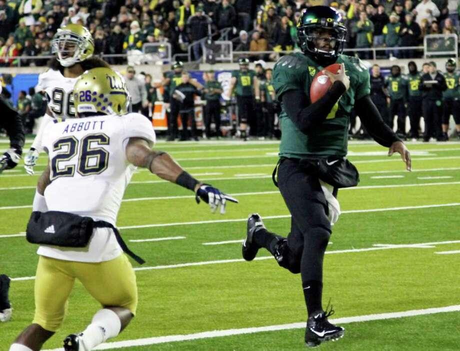 Oregon quarterback Darron Thomas makes his way into the end zone for a first-half touchdown. Photo: AP