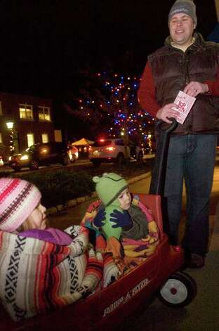 Olivia Carlson, 4, left, and her brother, Xavier Carlson, 2, sit bundled in their wagon as their father, Chris Carlson, eats popcorn during the 12th annual Holiday Stroll in Ridgefield on Friday, Dec. 2, 2011. Photo: Jason Rearick / The News-Times