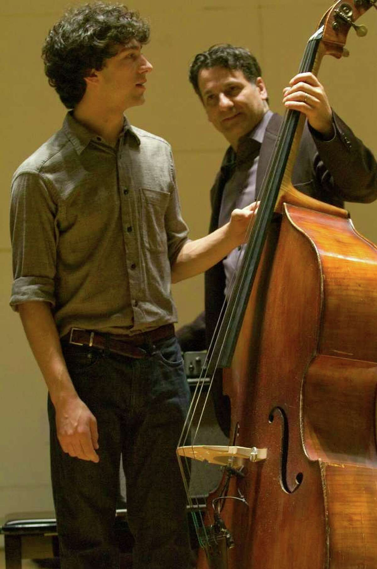 Jazz musician John Patitucci, right, hands Western Connecticut State University student Silvain Castellano his upright bass to play during Patitucci's visit to WestConn on Friday, Dec. 2, 2011.