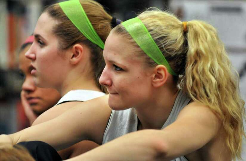 Shenendehowa girls' basketball player Emily Weber, at right, listens as coach Ken Strube   announce'