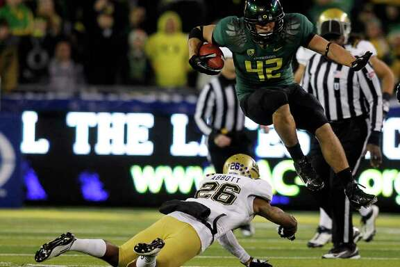JONATHAN FERREY : GETTY IMAGES DUCKS ROLL: Oregon's David Paulson (42) leaps over UCLA's Andrew Abbott during the Ducks' 49-31 win of the inaugural Pac-12 Championship Game on Friday.