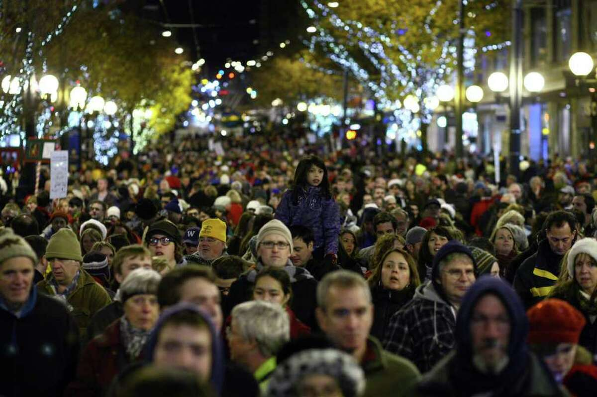 Spectators line Pine Street during the 25th annual Great Figgy Pudding street corner caroling competition on Friday, December 2, 2011 in downtown Seattle. The event is a fundraiser for the Pike Market Senior Center & Downtown Food Bank.