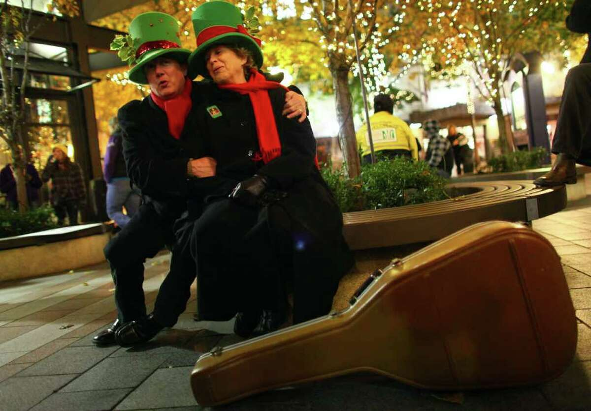 Matt Llewellyn and Barbara Roper practice their tunes during the 25th annual Great Figgy Pudding street corner caroling competition.