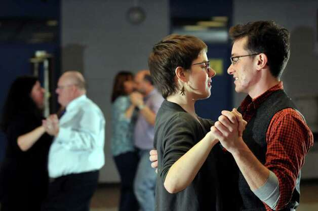 Christopher Argyros, right, learns dance steps with his girlfriend Laura Blosser during ballroom dance lessons on Thursday, Nov. 3, 2011, at Albany High in Albany, N.Y. Instructor Hershell Allen, left, watches their progress. (Cindy Schultz / Times Union) Photo: Cindy Schultz