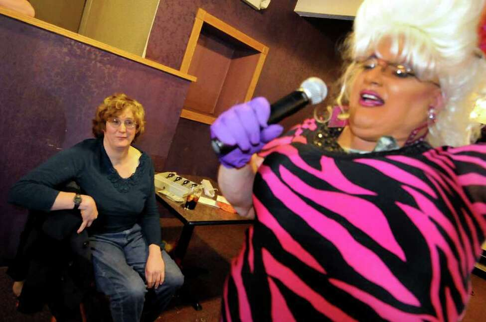 Transgender woman Robin Muse of Albany, left, who's in charge of selling tickets for the drag show, watches housemate Frieda Munchon perform on Sunday, Nov. 6, 2011, at the Irish Mist in Troy, N.Y. (Cindy Schultz / Times Union)