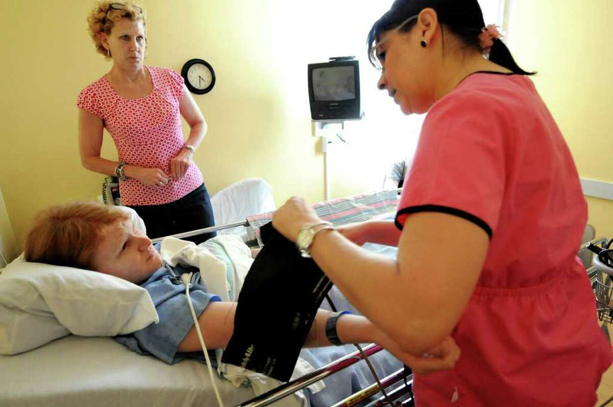 Feeling numb from an epidural, Drew Cordes and her mother, Janet, talk with a nurse after surgery on Monday, May 30, 2011, at Centre Metropolitain de Chirurgie Plastique in Montreal, Quebec in Canada. (Cindy Schultz / Times Union)