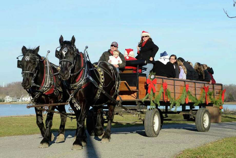 People enjoy a hayride with Santa at Cove Island Park in Stamford, CT on Sat., Dec. 3, 2011. This is the twelfth year the ticketed event has been offered by Stamford Recreation Services, and they expect 500 riders on Saturday, and 275 during shorter hours on Sunday. Photo: Shelley Cryan / Shelley Cryan freelance; Stamford Advocate freelance