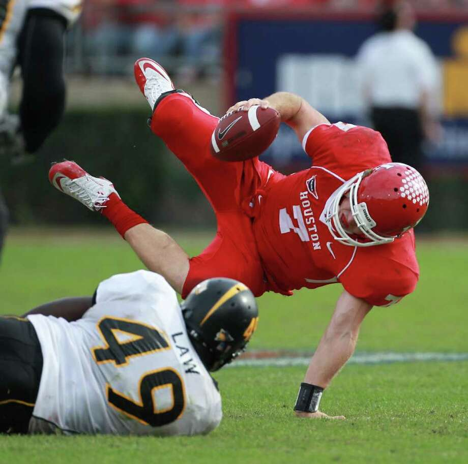 University of Houston quarterback Case Keenum (7) is sacked by University of Southern Mississippi defensive lineman Cordarro Law (49) during the fourth quarter of the 2011 Conference USA Football Championship game, Saturday, Dec. 3, 2011, in Robertson Stadium in Houston. The University of Southern Mississippi won 49-28. Photo: Nick De La Torre, Houston Chronicle / © 2011  Houston Chronicle