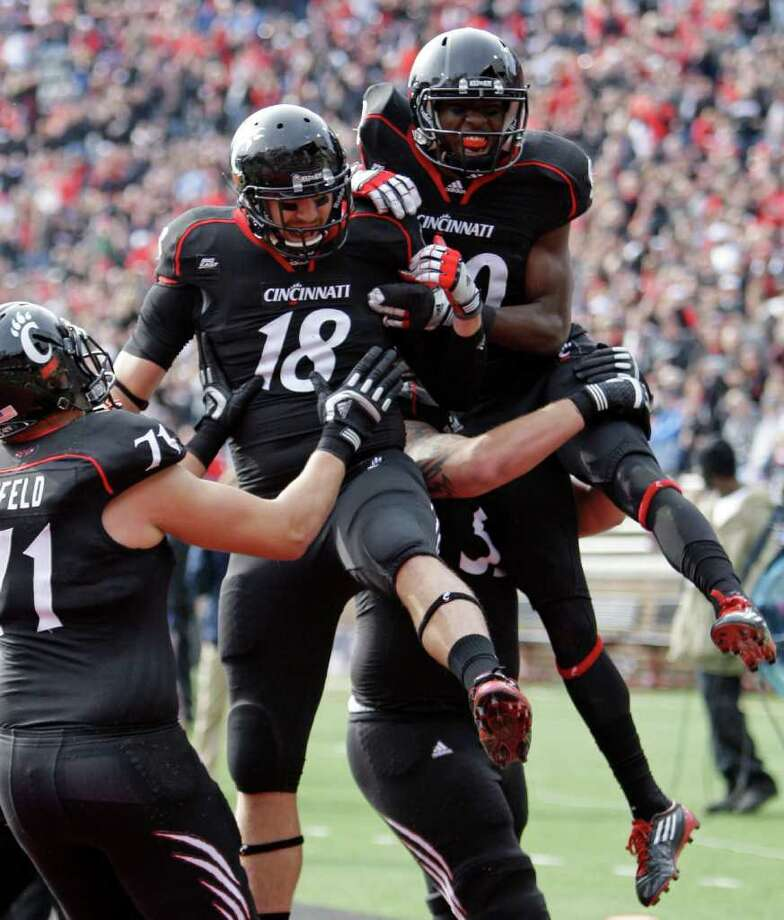 Cincinnati tackle Eric Lefeld (71), tight end Travis Kelce (18), and receiver Alex Chisum celebrate after Chisum caught a 22-yard touchdown pass against Connecticut in the first half of an NCAA college football game, Saturday, Dec. 3, 2011, in Cincinnati, Ohio. (AP Photo/Al Behrman) Photo: Al Behrman, Associated Press / AP