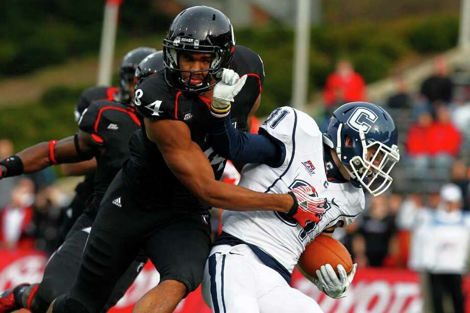CINCINNATI, OH - DECEMBER 03:  Nick Williams #31 of the Connecticut Huskies pulls Orion Woodard #84 of the Cincinnati Bearcats down by the facemask on December 3, 2011 at Nippert Stadium in Cincinnati, Ohio. Cincinnati defeated Connecticut 35-27. (Photo by Tyler Barrick/Getty Images) Photo: Tyler Barrick, Getty / 2011 Getty Images