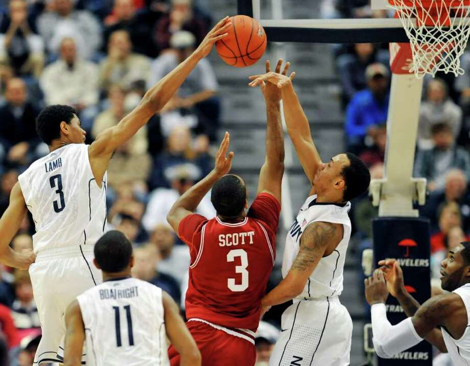 Connecticut's Jeremy Lamb, top left, blocks a shot by Arkansas' Rickey Scott (3) as Connecticut's Shabazz Napier, second from right, defends and teammates Ryan Boatright (11) and Alex Oriakhi, bottom right, look on in the first half of an NCAA college basketball game in Hartford, Conn., Saturday, Dec. 3, 2011. (AP Photo/Jessica Hill) Photo: Jessica Hill, Associated Press / AP2011