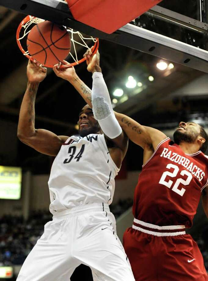 Connecticut's Alex Oriakhi, left, dunks the ball while guarded by Arkansas' Marvell Waithe (22) in the first half of an NCAA college basketball game in Hartford, Conn., Saturday, Dec. 3, 2011.  (AP Photo/Jessica Hill) Photo: Jessica Hill, Associated Press / AP2011