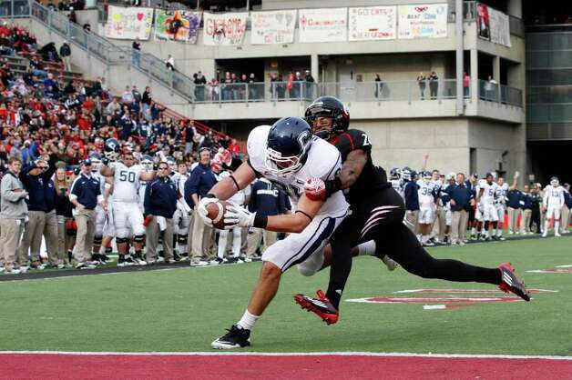 UConn's Corey Manning runs past Cincinnati's Chris Williams into the end zone to score a 2-point conversion at Nippert Stadium in Cincinnati, Ohio. Cincinnati defeated Connecticut 35-27. Photo: Tyler Barrick/Getty Images / 2011 Getty Images
