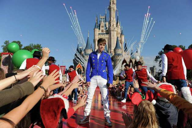 "In this photo provided by Disney, Justin Bieber performs  while taping a segment for the ""Disney Parks Christmas Day Parade"" TV special at the Magic Kingdom park at Walt Disney World in Lake Buena Vista, Fla.  on Saturday, Dec. 3, 2011.  (AP Photo/Disney, Mark Ashman) Photo: Mark Ashman"
