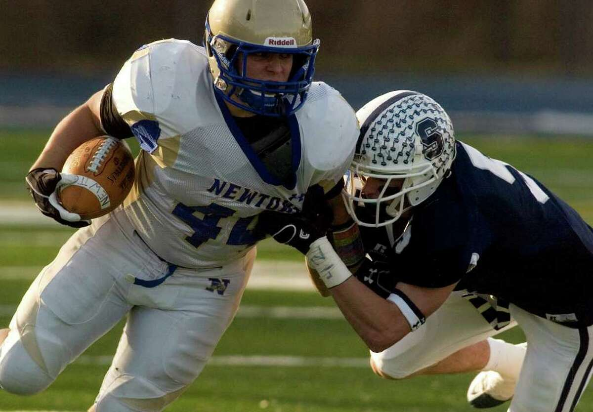 Louis Fenaroli runs the ball with pressure from Staples' Nick Kelly during their class LL semifinal game at Bunnell High School in Stratford on Saturday, Dec. 3, 2011. Staples won 44-20.