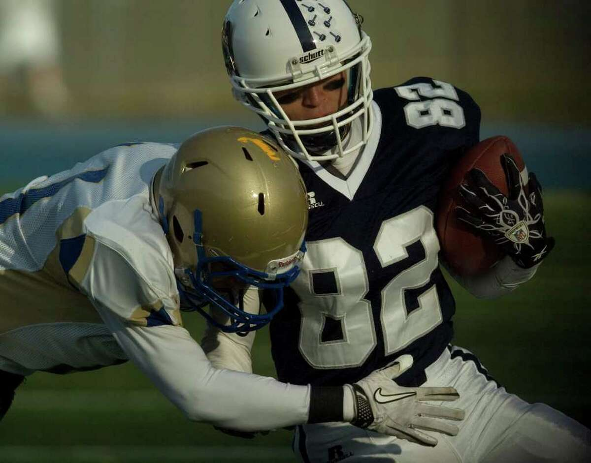 Staples' Zach Mitchell runs the ball while under pressure from Newtown's Jefferson Tolson during their class LL semifinal game at Bunnell High School in Stratford on Saturday, Dec. 3, 2011. Staples won 44-20.