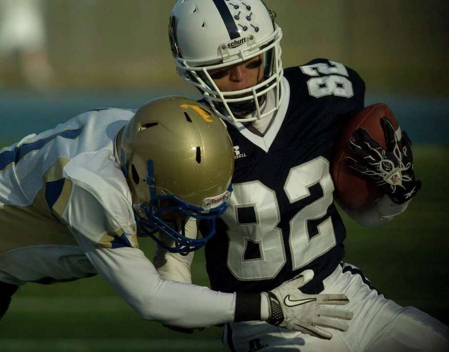 Staples' Zach Mitchell runs the ball while under pressure from Newtown's Jefferson Tolson during their class LL semifinal game at Bunnell High School in Stratford on Saturday, Dec. 3, 2011. Staples won 44-20. Photo: Jason Rearick / The News-Times