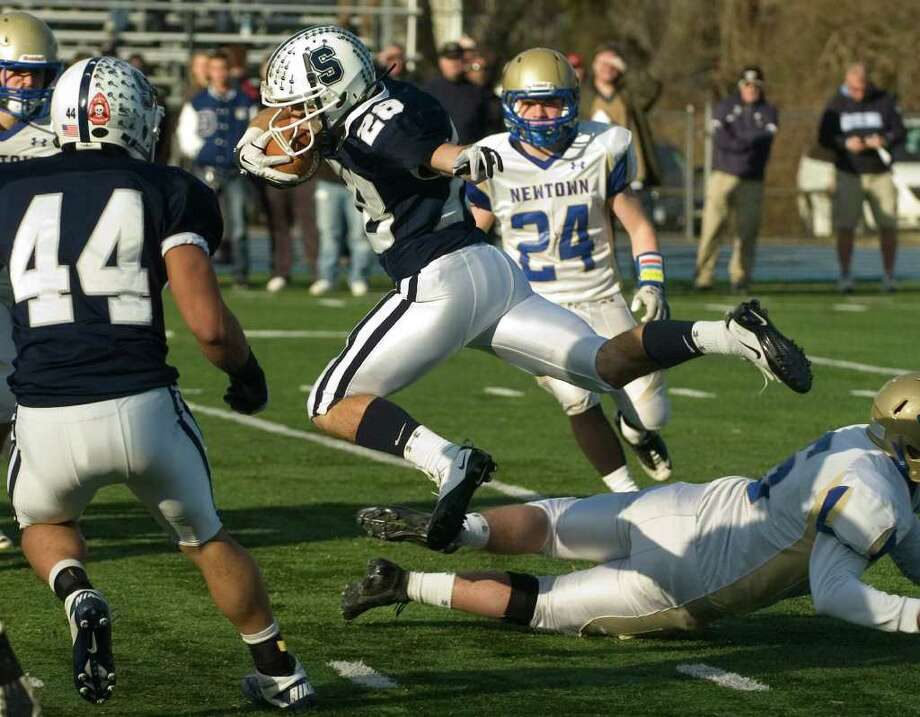 Staples' Jon Heil evades the Newtown defense during their class LL semifinal game at Bunnell High School in Stratford on Saturday, Dec. 3, 2011. Staples won 44-20. Photo: Jason Rearick / The News-Times
