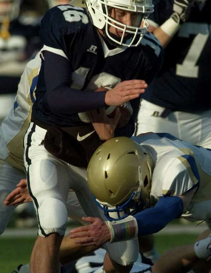 Staples quarterback Jack Massie is brought down after a short run by Newtown's Dan Hebert during their class LL semifinal game at Bunnell High School in Stratford on Saturday, Dec. 3, 2011. Staples won 44-20. Photo: Jason Rearick / The News-Times
