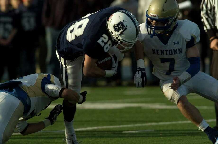 Staples' Jon Heil is brought down by Newtown's Justin Devellis, left, and Dan Hebert during their class LL semifinal game at Bunnell High School in Stratford on Saturday, Dec. 3, 2011. Staples won 44-20. Photo: Jason Rearick / The News-Times